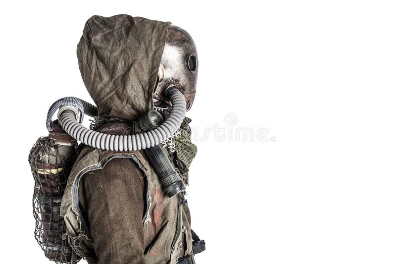 Post nuclear catastrophe survivor in gas mask. Scary post apocalyptic, living underground, creature with vintage lantern on shoulder, wearing rags and creepy royalty free stock image