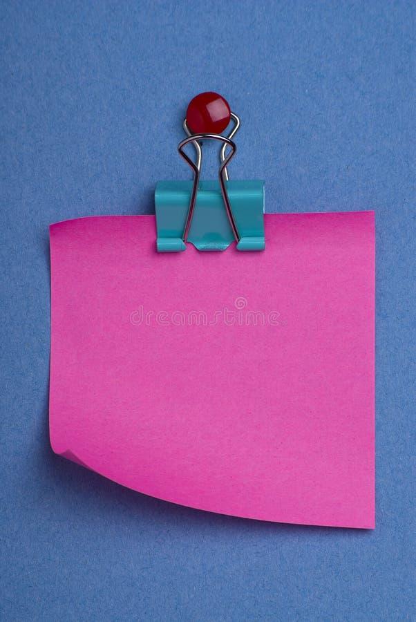 Post-it rosado en azul imagenes de archivo