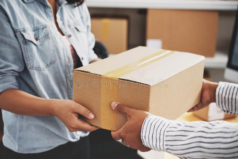 Post service. Female post worker giving parcel to customer stock photo