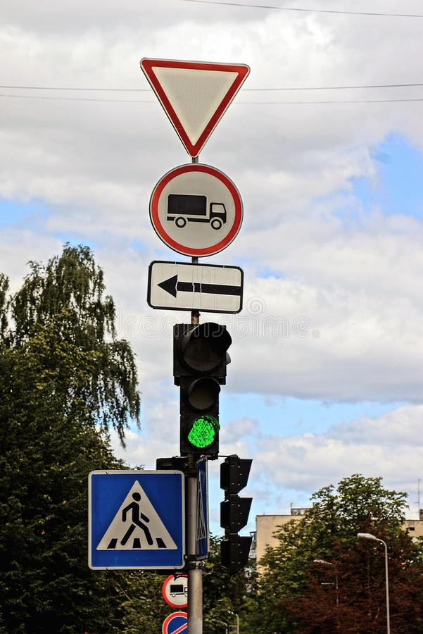 A post with traffic signs and a traffic light at a crossroads stock photo
