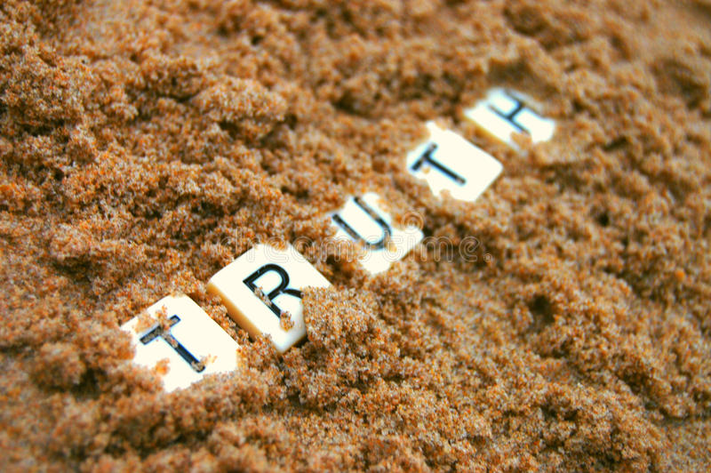 Post Truth. The letters of the word truth being buried in sand royalty free stock image