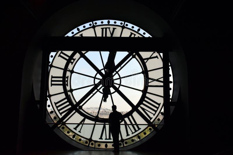 Postać mężczyzna przeciw tłu ogromny ścienny zegar fotografia stock