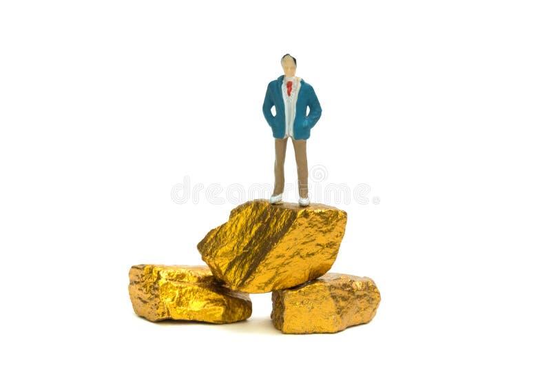 Postać miniaturowy biznesmen lub mali ludzie z stosem złoto n zdjęcia stock
