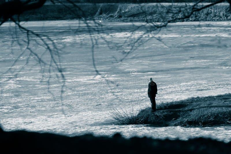 Postać osamotniony mężczyzna w czarnym kostiumu na przylądku po środku zamarzniętego stawu Kwiecień, wiosna Czarny i biały stonow zdjęcia stock