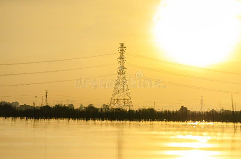 Posta ad alta tensione sulla vista del paesaggio alla mattina con giallo del cielo ed il fondo del fiume immagine stock