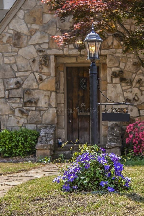 Posta d'annata della lampada con la clematide porpora in pieno delle fioriture che vining intorno al fondo e della porta rustica  immagine stock