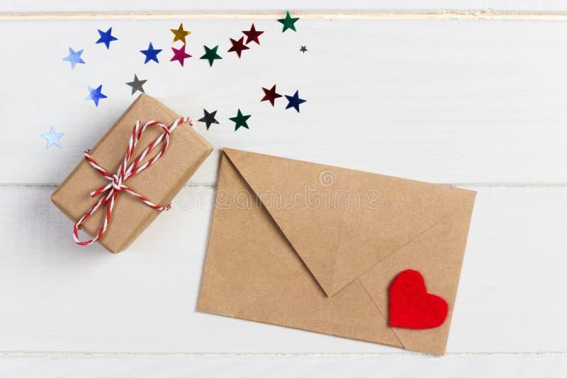 Posta della busta con la scatola rossa di regalo e del cuore sopra fondo di legno bianco Concetto di saluto di Valentine Day Card fotografie stock