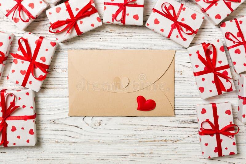 Posta della busta con la scatola rossa di regalo e del cuore sopra fondo di legno Progettazione di massima di saluto di Valentine immagini stock libere da diritti