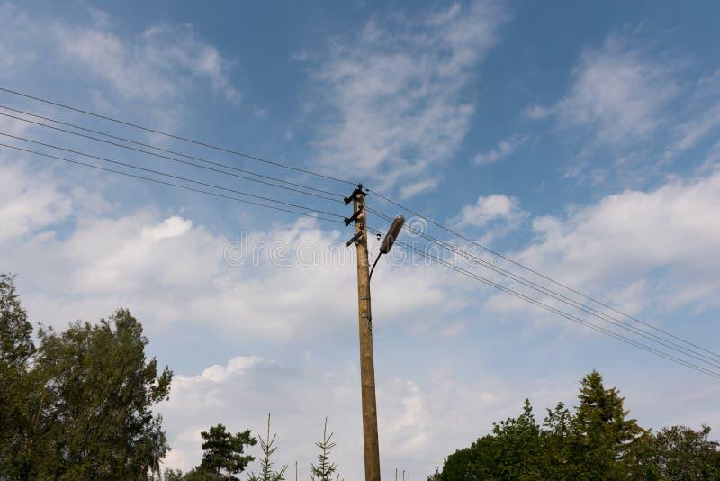 Posta di legno della lampada di via con i cavi elettrici contro cielo blu con le nuvole bianche immagini stock libere da diritti