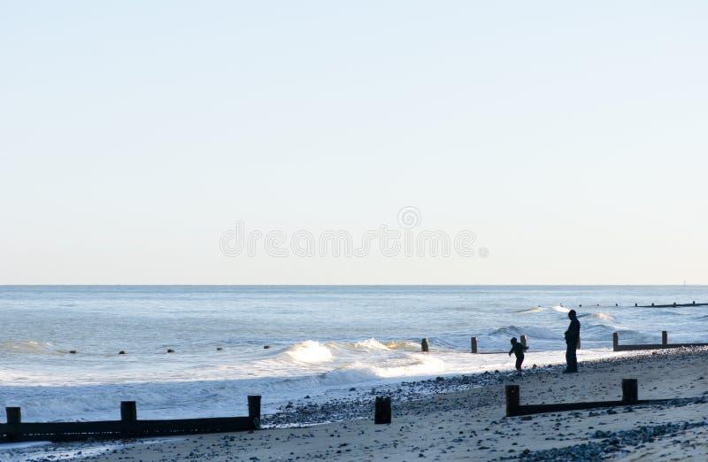 Postacie sylwetkowe na wieczór wyrzucać na brzeg w Anglia. fotografia royalty free