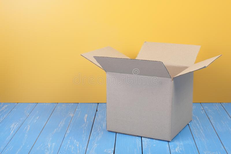 Postage and packing service - Open square small Package. Postage and packing service - Open Package on a blue wood and yellow wall background stock image
