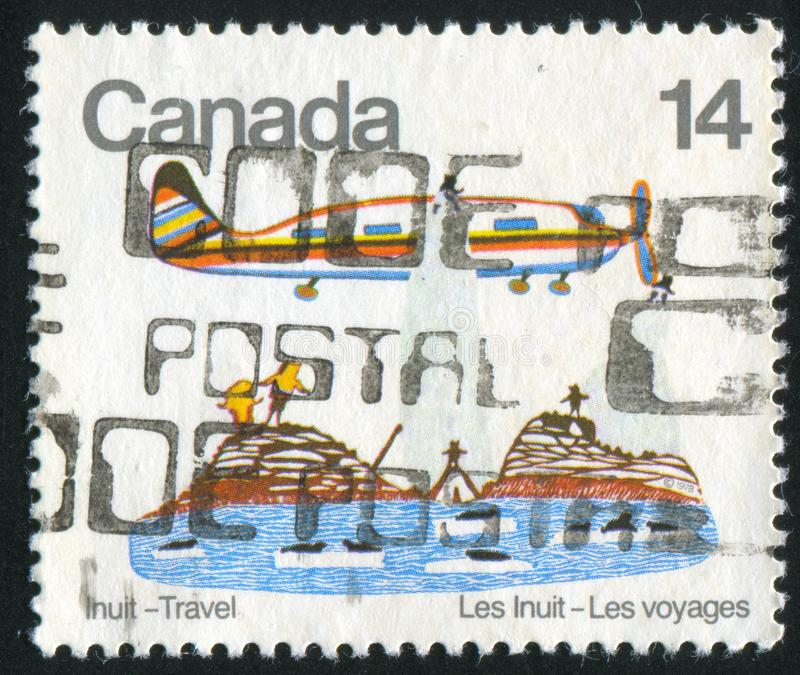 Postage stamp. CANADA - CIRCA 1978: stamp printed by Canada, shows Plane over village, stonecut and stencil print by Pudlo, circa 1978 royalty free stock photo