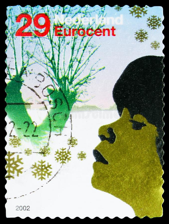 Postage stamp printed in Netherlands shows Persons in winter landscape, December Stamps serie, circa 2002 royalty free stock image