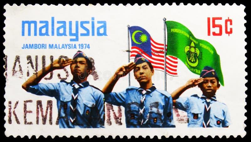 Postagstämpel i Malaysia visar Scouts saluting, flaggor, Malaysian Scout Jamboree serie, circa 1974 arkivfoton