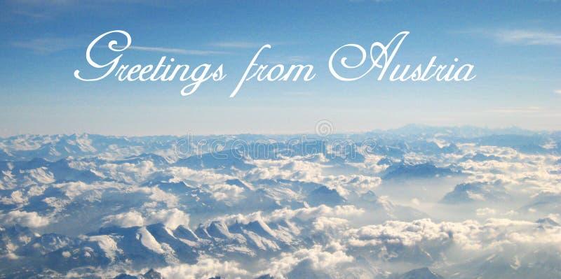 Postal con maravillosamente una opinión del panorama de un vuelo sobre las nubes y las montañas nevosas en un día soleado foto de archivo