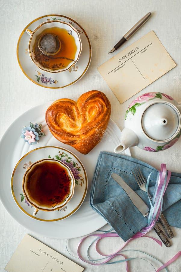 Postal con té y el bollo del dulce en la tabla blanca imagenes de archivo