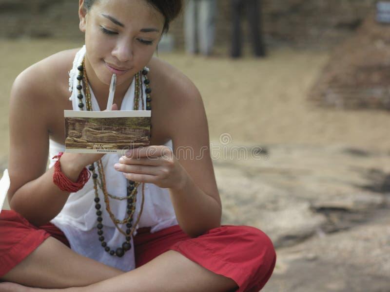 Postal de la lectura de la mujer de la raza mixta al aire libre foto de archivo libre de regalías