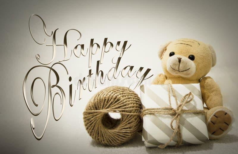 Postal del feliz cumpleaños con el pastel del oso de peluche y de la caja de regalo fotografía de archivo