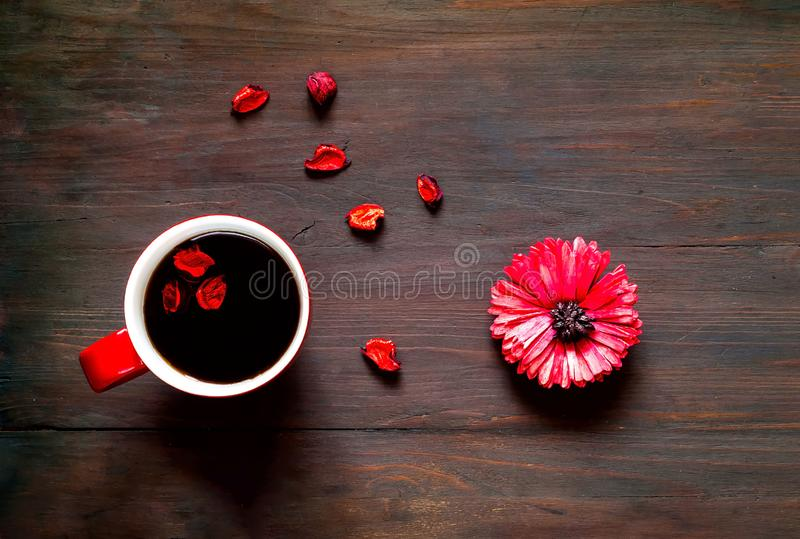 Postal del saludo del día de tarjetas del día de San Valentín Flor y taza de café roja grande en fondo de madera Concepto festivo fotografía de archivo