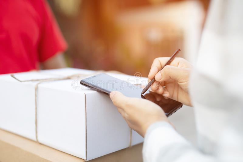 Postal delivery man of a package through a service. Young woman accepting signature in digital mobile phone of box after receiving parcel from courier at home stock photo