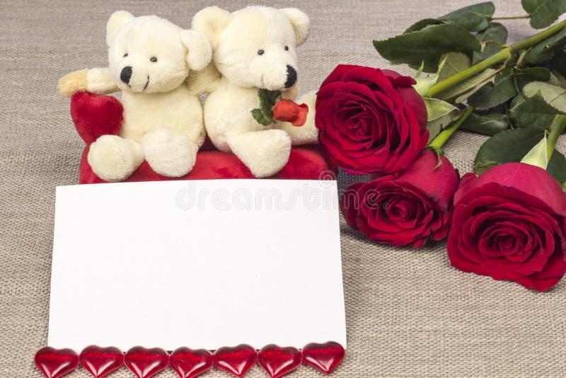 Postal el día de tarjetas del día de San Valentín con las rosas y el juguete imagen de archivo