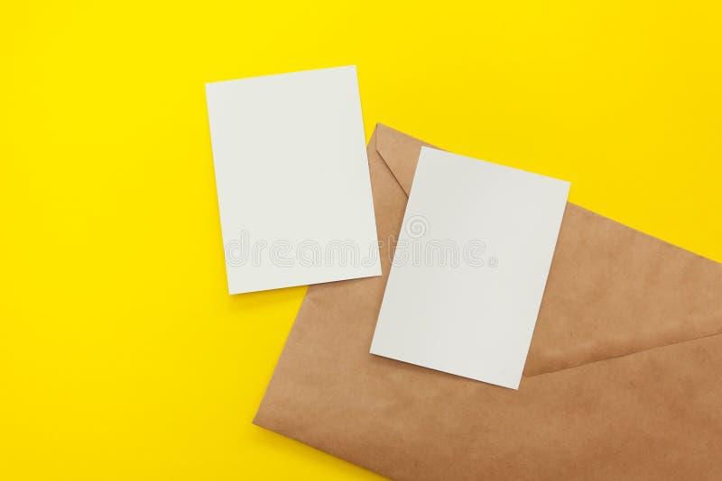 Postal en blanco dos con el sobre marrón en fondo amarillo fotos de archivo libres de regalías