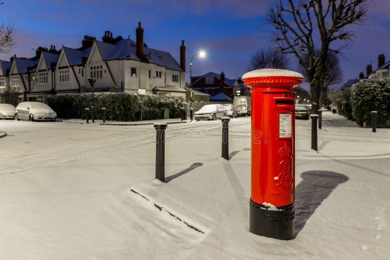 Postbox in sneeuw in de voorstad van Londen, het UK royalty-vrije stock fotografie