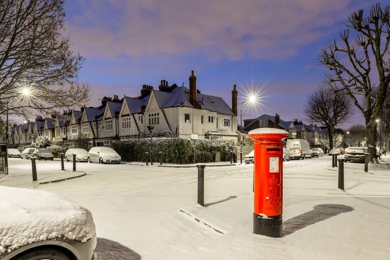 Postbox in sneeuw in de voorstad van Londen, het UK stock fotografie