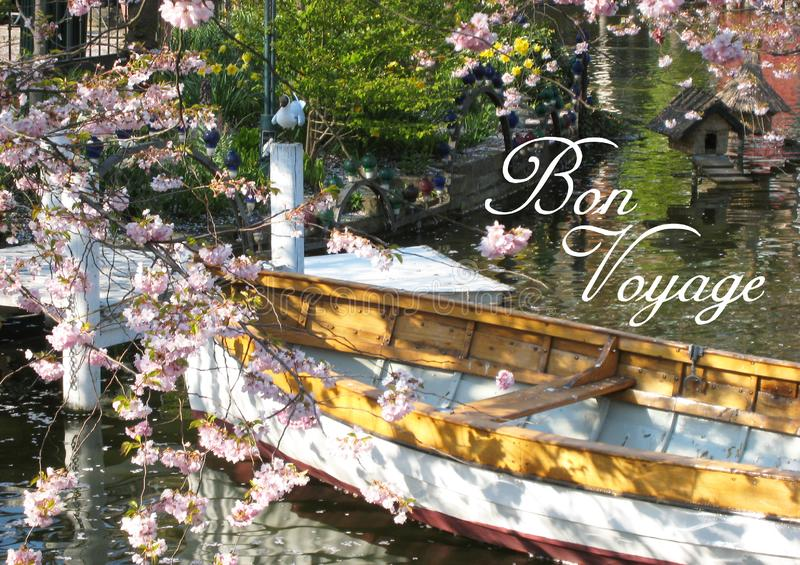Postcard with a beautifully view of a wooden boat in Copenhagen in Denmark surrounded by a sea of ​​flowers in a small lake royalty free stock photography