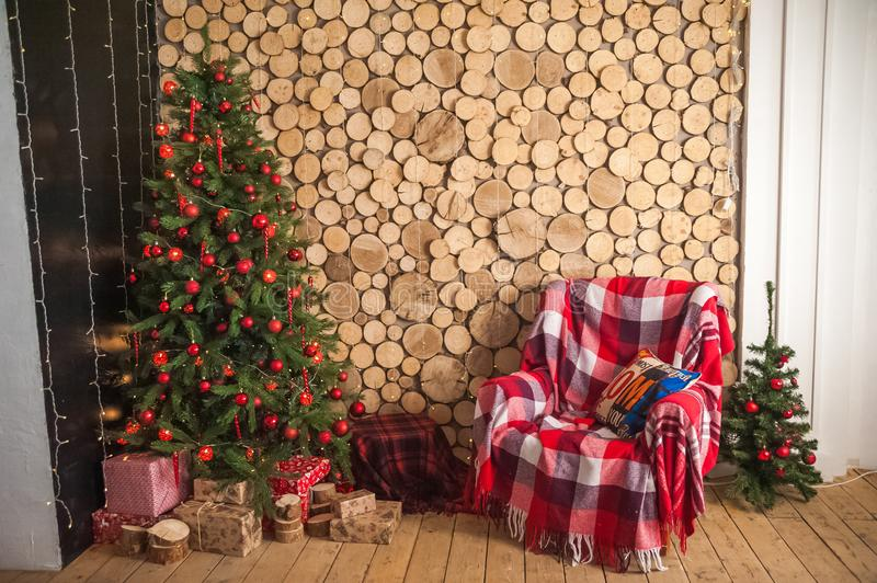 Postcard from a Christmas tree with an armchair and copy space. Details of a decorated interior with gifts with a frame for text. royalty free stock images