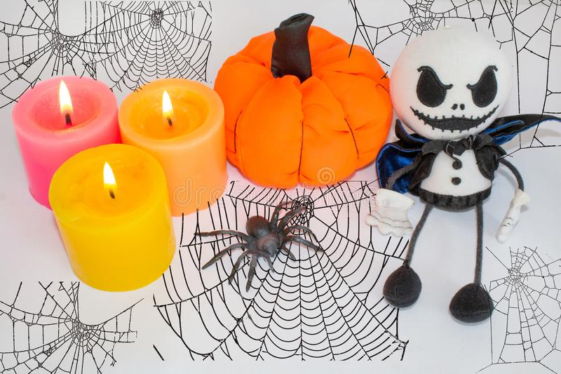 Postcard for Halloween, candles with pumpkin, spider and ghost doll. On a red background with a cobweb. Postcard for Halloween, candles with a pumpkin, a spider royalty free stock images