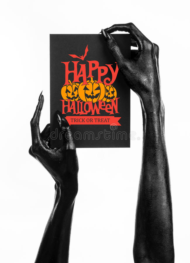 Postcard and Happy Halloween theme: black hand of death holding a paper card with the words Happy Halloween on a white isolated ba. Ckground royalty free stock image