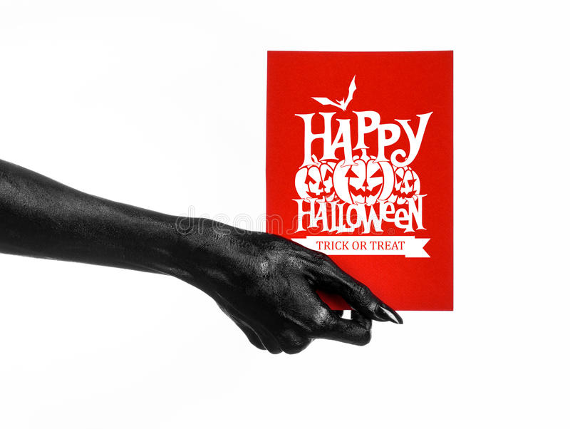 Postcard and Happy Halloween theme: black hand of death holding a paper card with the words Happy Halloween on a white isolated ba. Ckground royalty free stock photo