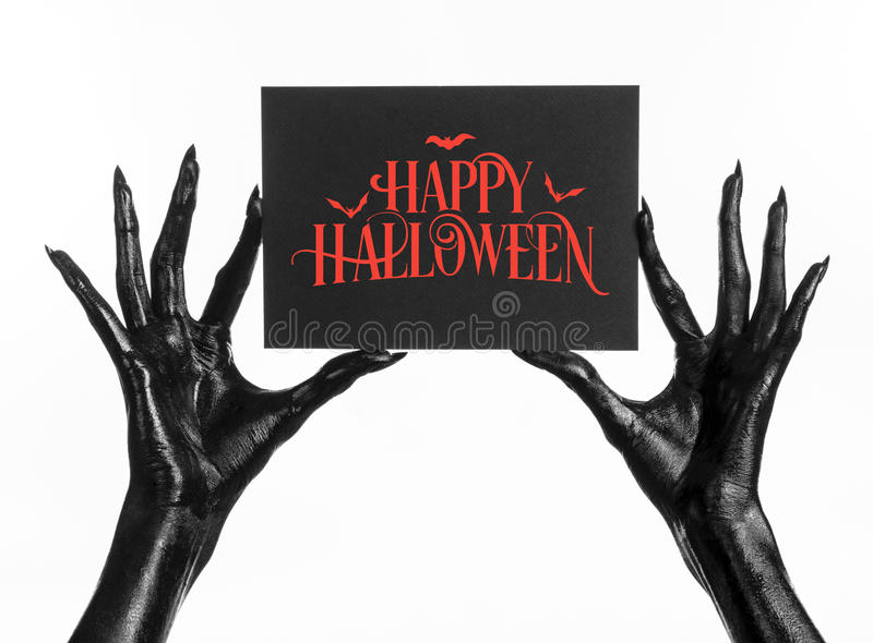 Postcard and Happy Halloween theme: black hand of death holding a paper card with the words Happy Halloween on a white isolated ba. Ckground stock photography