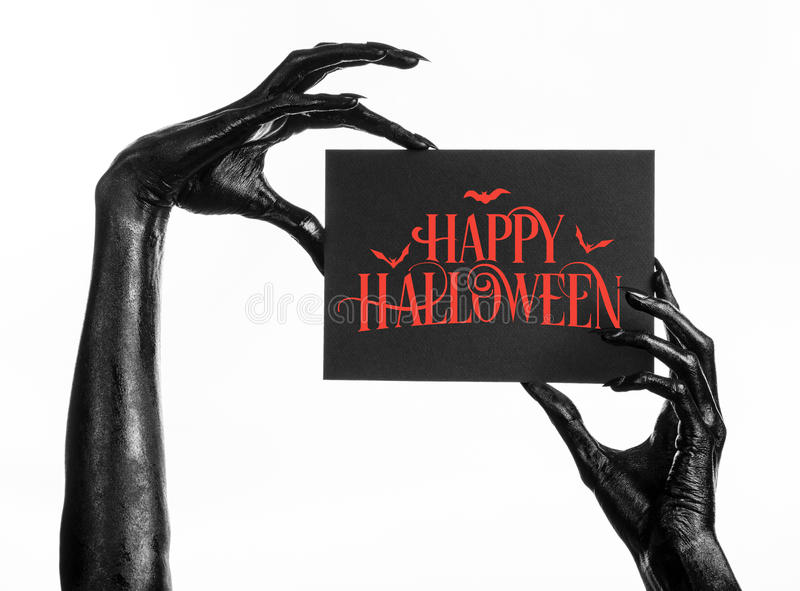 Postcard and Happy Halloween theme: black hand of death holding a paper card with the words Happy Halloween on a white isolated ba. Ckground royalty free stock photography