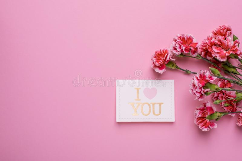 Postcard I love you with pink flowers on a pink background. Top view stock image