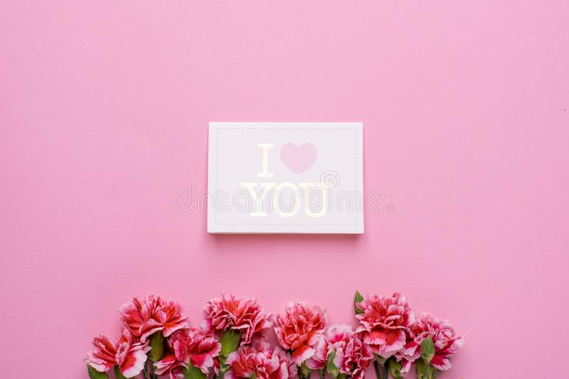 Postcard I love you with pink flowers on a pink background. Top view stock photo