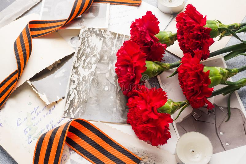 Postcard may 9 - red carnations Ribbon George Old photos on a concrete background. Symbol of victory in the great Patriotic war.  royalty free stock photo