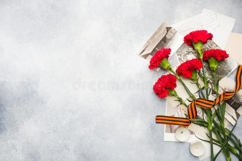 Postcard may 9 - red carnations Ribbon George Old photos on a concrete background. Symbol of victory in the great Patriotic war.  stock photography