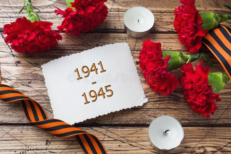 Postcard may 9 - red carnations Ribbon George Old photos on a wooden background. Symbol of victory in the great Patriotic war stock photography