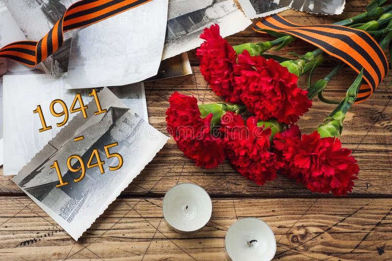 Postcard may 9 - red carnations Ribbon George Old photos on a wooden background. Symbol of victory in the great Patriotic war.  stock photography