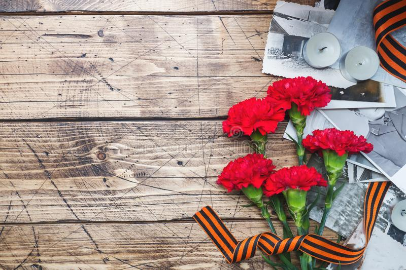 Postcard may 9 - red carnations Ribbon George Old photos on a wooden background. Symbol of victory in the great Patriotic war.  stock photos