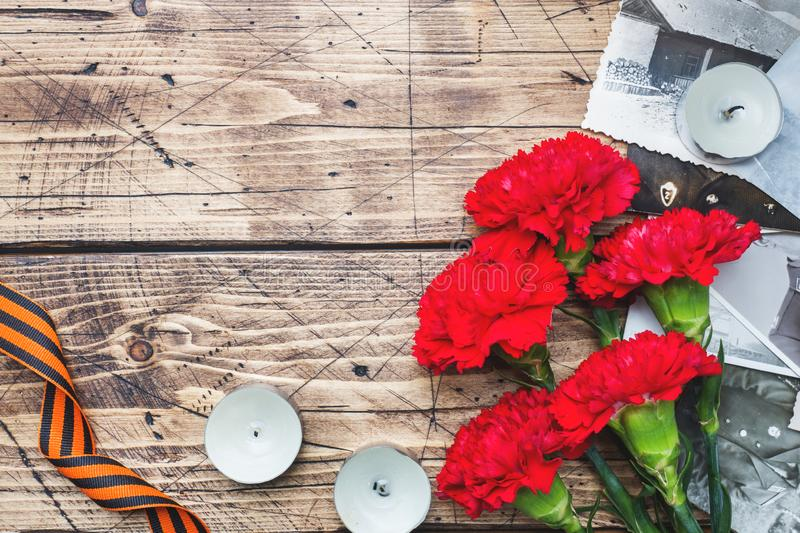 Postcard may 9 - red carnations Ribbon George Old photos on a wooden background. Symbol of victory in the great Patriotic war.  royalty free stock photos