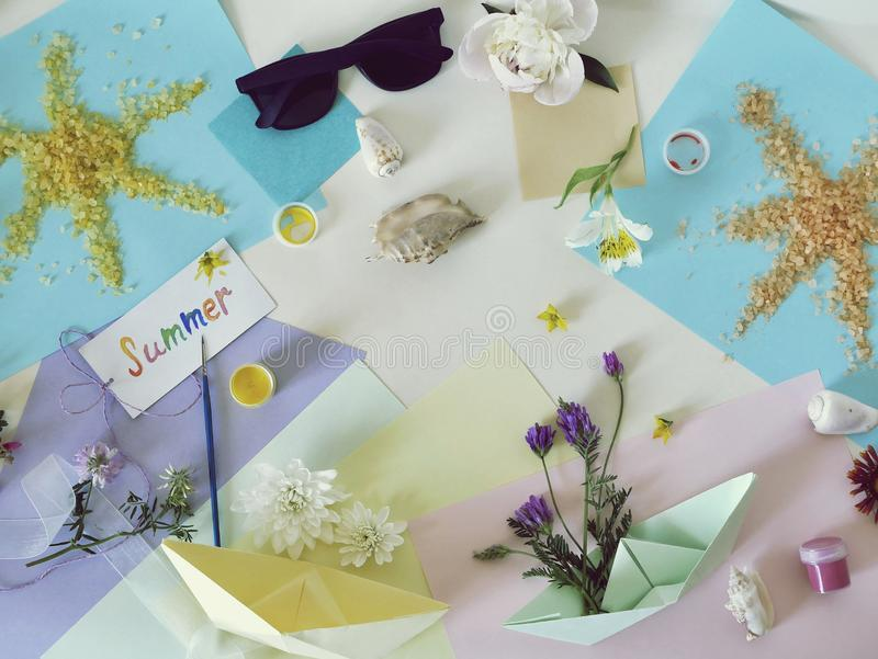 Postcard summer, the sun from sea salt, fresh flowers, colored paper, brushes - the concept of congratulations on the summer stock image