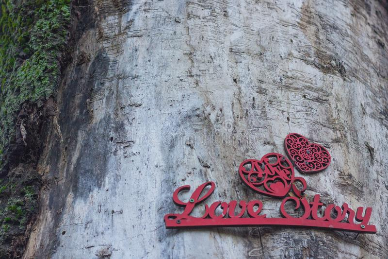 Romantic wooden background with the inscription love story. Postcard for Valentine`s Day. Romantic wooden background with the inscription Love Story. A stock photography