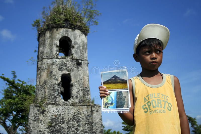 Postcard vendor cagsawa church philippines. Small boy working in the hot sun selling postcards in front of cagsaw church ruins and the mount mayon volcano in the royalty free stock images