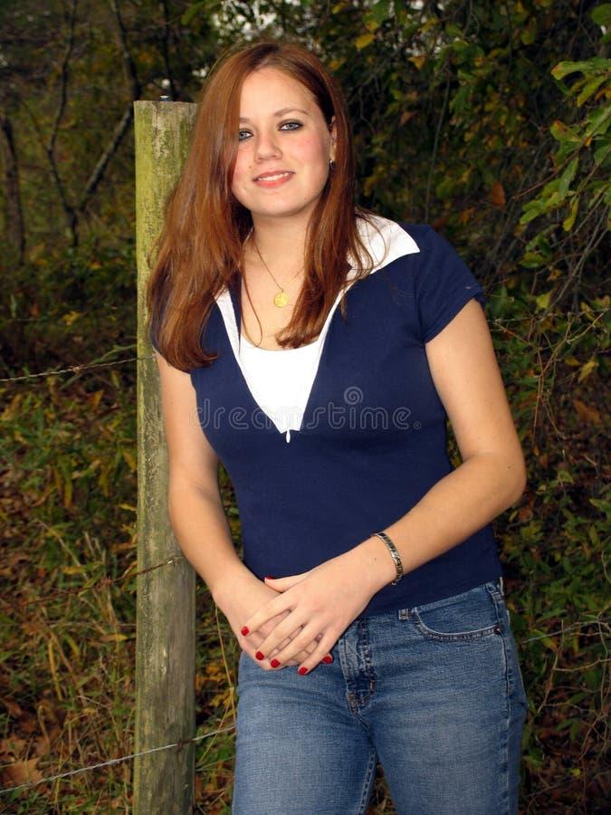 Poste bonito de la muchacha y de la cerca foto de archivo