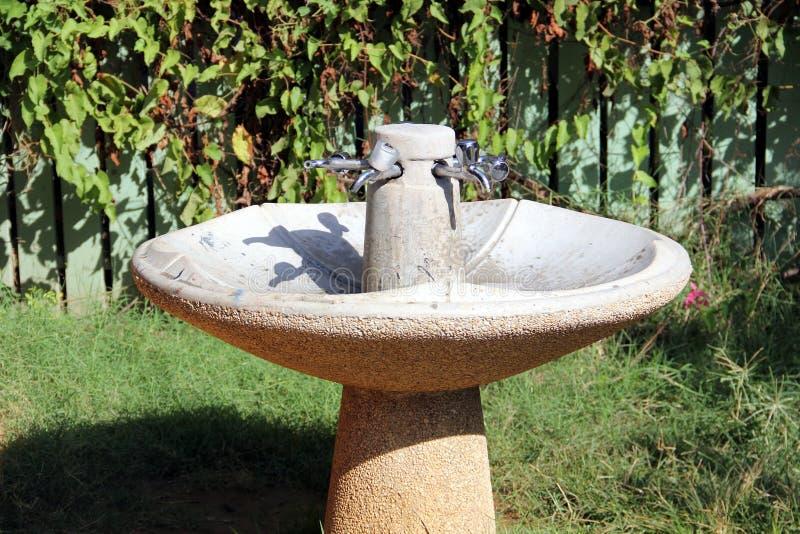 Poste d'eau potable avec quatre robinets et évier en pierre photo stock