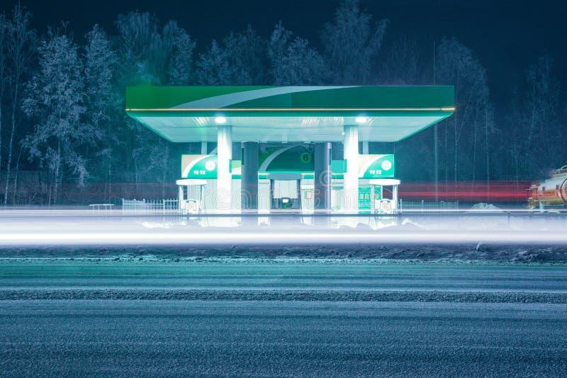 Poste d'essence d'hiver la nuit avec de longues voies légères des phares de passer des voitures image stock