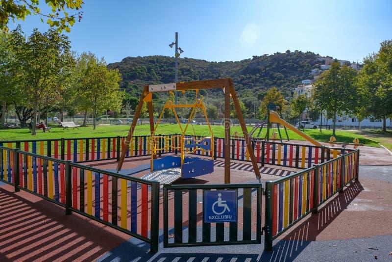Poste de ala para niños con discapacidades en silla de ruedas en el patio de recreo fotografía de archivo